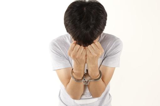 人物 男性 若者 手 手錠 犯罪 犯人 犯罪者 逮捕 検挙 事件 窃盗 詐欺 傷害 罪 現行犯 容疑者 捕まえる 正面 白バック 白背景 アップ Tシャツ 上半身 顔を隠す 後悔 違法行為 不法行為 捕まる