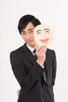 日本人 笑顔 仮面 裏の顔 ニヤリ ニヤニヤ 含み笑い マスク 男性 男の人 人間 人物 若い 30代 スーツ ネクタイ ビジネスマン 会社 社会人 社員 職員 政治家 議員 白背景 白バック 不祥事 お金 汚職 詐欺 献金 政治 mdjm005