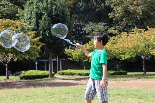しゃぼん玉で遊ぶ子供の写真
