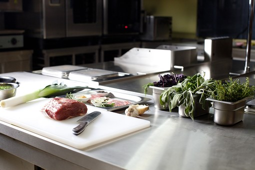 厨房 台所 キッチン 料理 調理 肉 ブロック肉 長ネギ 白ネギ 玉ねぎ ニンニク オニオン ガーリック 包丁 まな板  カッティングボード 銀色 シルバー ナイフ 下準備 下ごしらえ 仕込み 野菜 ベジタブル 材料 レシピ  具材 薄暗い 食材