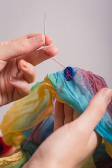 ソーイング 縫い物 裁縫 洋裁 手芸  手仕事 裁縫道具 裁縫用品 アップ 素材  趣味 ハンドメイド ホビー 生活 暮らし  小物 手縫い ファッション 縫う 針仕事 手 手元 部分 針 糸 布 繕う 白バック 白背景