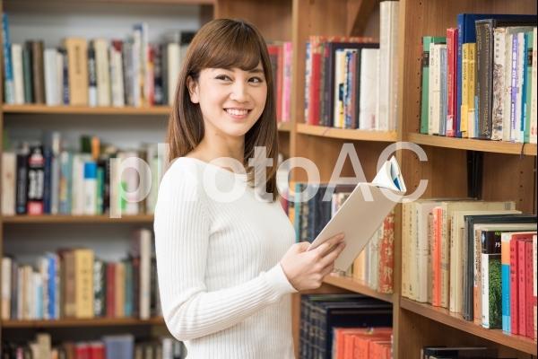 図書館で本棚の前に立って本を読む女子大生1の写真