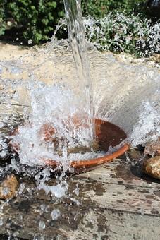 自然 植物 木 樹木 葉 葉っぱ 緑 水 水飛沫 透明 水玉 雫 注ぐ 勢い 強い 水流 跳ねる 濡れる 板 器 皿 土 地面 無人 アップ 屋外 室外 景色 風景 景観