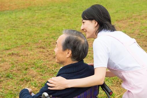 屋外の車椅子の男性と介護士10の写真