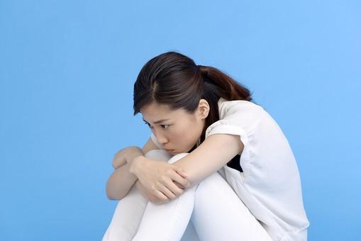 女性 ポーズ 人物 30代 日本人 黒髪 爽やか カジュアル 屋内 横向き ブルーバック 青背景 半そで 白  腕組 全身 苦しい つらい 悲しい 悲痛 悲惨 肩を落とす 悲嘆 嘆く 諦め がっくり 絶望 黒 靴 座る 足 抱える ふてくされる mdjf013