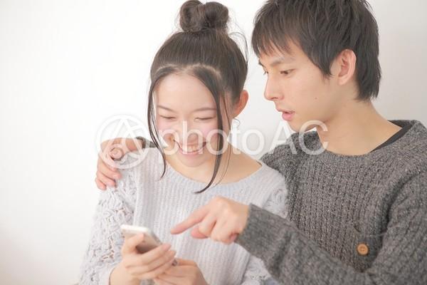スマホを見ているカップルの写真