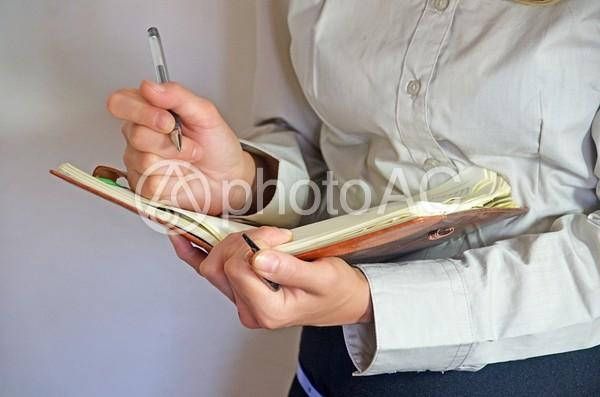 手帳にメモするビジネスウーマンの写真