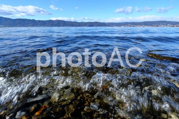 風波の押し寄せる諏訪湖の湖岸の写真