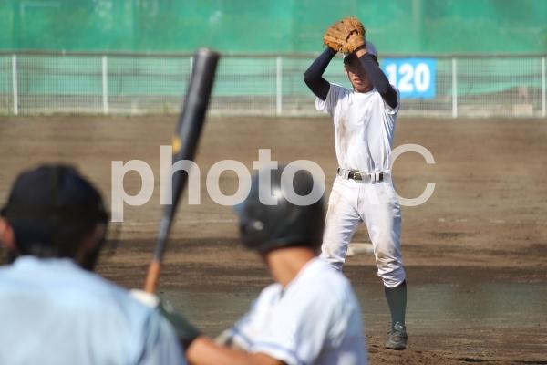 高校野球・相手強打者に立ち向かい一球目を投じる右投げ本格派のエースピッチャーの写真