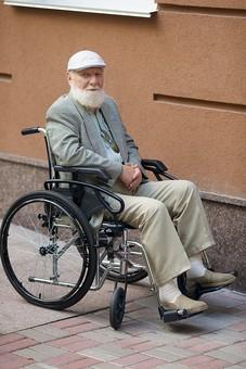 病院 医院 診療所 屋外 外 外国人 白人 男性 老人 高齢 高齢者 おじいさん おじいちゃん 髭 ヒゲ ひげ 白髪 車椅子 車いす 座る 乗る 乗せる 上着 ジャケット ハンチング帽 全身 カメラ目線 mdjms016