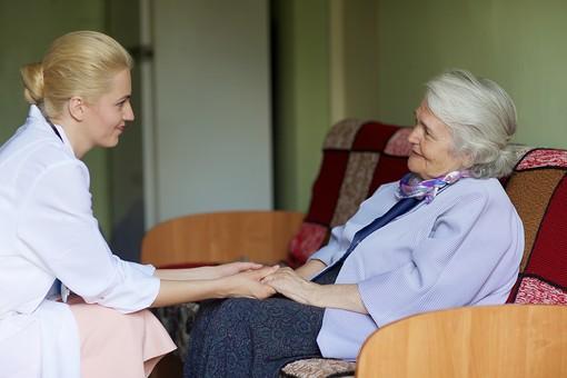 室内 屋内 外国人 老人 高齢者 女性 おばあさん おばあちゃん 患者 白髪 白人 女医 金髪 白衣 医師 医者 病院 病室 個室 家 自宅 ベッドルーム ソファー ソファ 座る 手をつなぐ 手を握る 両手 見守る 寄り添う 会話 話す しゃべる 訪問 訪問診療 mdff142 mdfs017
