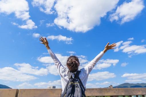 青空に向かってバンザイをする女性の写真