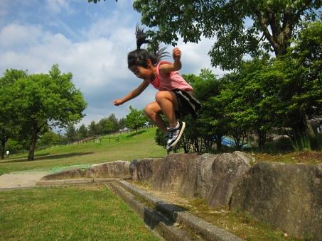 子ども ジャンプ 遊ぶ じゃんぷ 跳ぶ とぶ 飛ぶ 緑 癒やし グリーン 新緑 背景 植物 初夏 テクスチャ 余白 季節 5月 子供 こども 公園 女の子 女子 小学生