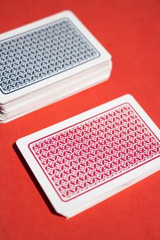 トランプ カード ゲーム 札 屋内 レッドバック 赤背景 娯楽 机 テーブル 裏側 裏 青 赤 模様 束   絵札   手品 マジック 遊び 重ねる 配る 切る カードゲーム  まとまり グループ 異種