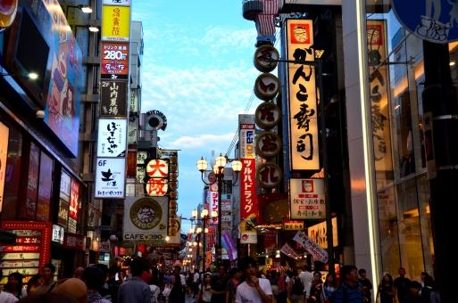 大阪市 中央区 ミナミ 道頓堀 歓楽街 繁華街 街角 雑踏 賑やか 人波 人混み ネオンサイン 看板 夕景 屋外 街並み 市街地 ビル 商業ビル 派手