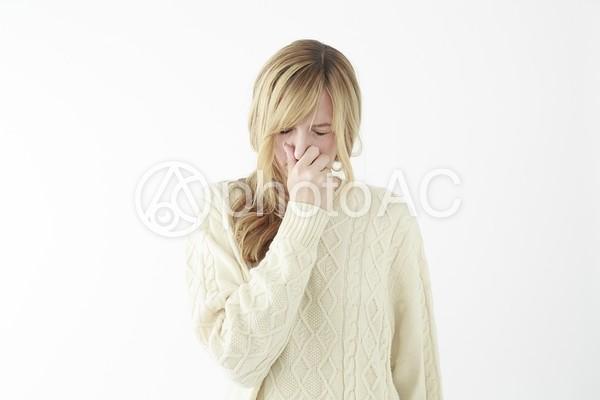 鼻を押さえる女性の写真