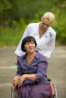 屋外 野外 外 病院 庭 公園 外国人 老人 高齢者 女性 おばあさん おばあちゃん 患者 女医 白人 金髪 白衣 医師 医者 スカート 車椅子 車いす 乗る 座る 押す 散歩 歩く 立ち止まる 止まる 話す 話しかける mdfs016 mdff142