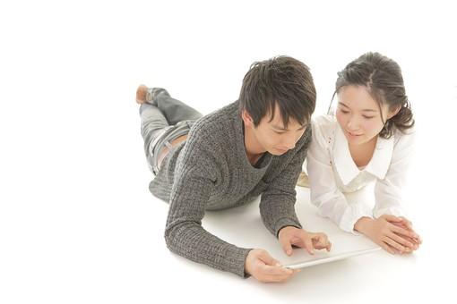 人物 男性 男子 女性 女子 若い デート カップル アベック 夫婦 新婚 白バック 白背景 部屋 リビング くつろぐ リラックス 仲良し 寝転ぶ タブレット 情報 検索 情報端末 インターネット 画面 日本人 mdjm008 mdjf026