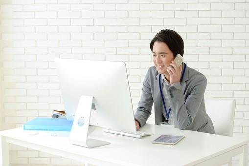 日本人 男性 男 20代 若い ファッション カジュアル インフォーマル 仕事 オフィス 会社 クリエイター デザイナー グラフィックデザイナー webデザイナー シャツ ストライプ 笑顔 スマイル 微笑み にこやか 爽快 爽やか パソコン PC デスクトップパソコン 机 テーブル 椅子 イス 携帯端末 スマホ スマートフォン タブレット タブレット端末 ファイル 会話 通話 話す 連絡 ビジネス ネームホルダー mdjm024