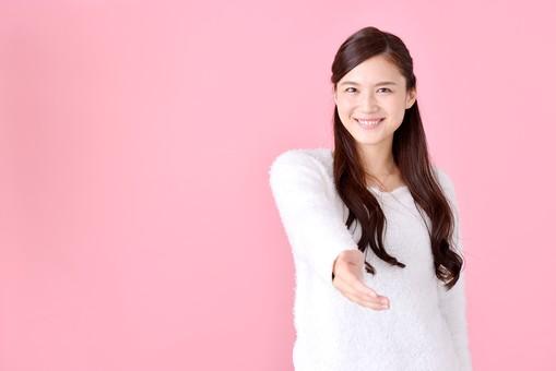 人物 女性 日本人 若者 若い  20代 美人 かわいい ロングヘア カジュアル  ラフ 私服 セーター ニット 屋内  スタジオ撮影 背景 ピンク ピンクバック ポーズ  おすすめ 手 片手 差し出す 握手 仲直り 自己紹介 正面 笑顔 上半身 mdjf007