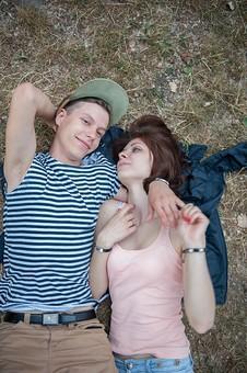 外国人 人物 カップル デート 男女 二人 美女 美男 男性 女性 白人 仲良し ラブラブ  屋外 野外 公園 自然 パーク 半袖 春 夏 秋 帽子 ボーダー 見つめる 見つめ合う 寝転がる 寄り添う 芝 mdfm001 mdff001