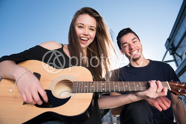 青空の下でギターを弾く男女16の写真