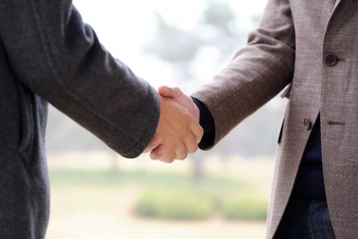 屋外で握手をするイメージの写真