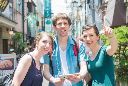 スマホを使う外国人観光客グループ3の写真