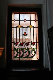 ステンドグラス ガラス シルエット 太陽光 浮かぶ 芸術 美術品 インテリア モチーフ 植物 明るい チューリップ つぼみ 花 茎 緑 赤 黄色 カーテン 窓 木枠 シンプル 豪華 洋風 明かり