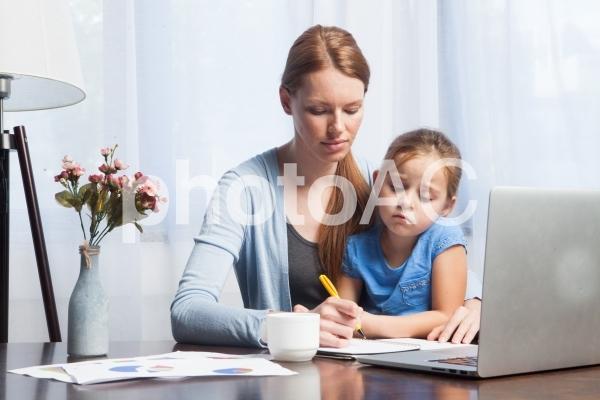自宅で娘を抱っこしながら仕事するお母さん3の写真