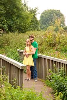 人物 外国人 外人 男性 女性 カップル 恋人 夫婦 2人 屋外 野外 外 自然 緑 グリーン 公園 手すり 柵 休日 デート 寄り添う 肩を寄せる 笑顔 スマイル 仲良し 散策 楽しい 幸せ 抱き寄せる 全身 mdff084 mdfm051