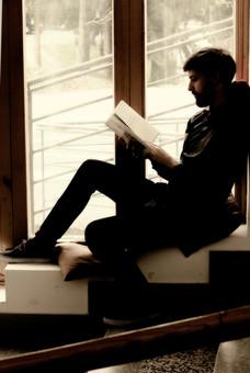 本 ブック 書物 書籍 図書 読書 読む 趣味 勉強 人物 男性 男 外国人 若い 若者 髭 20代 全身 ページ 捲る めくる 開く 座る 段差 段々 横顔 クッション 窓際 窓辺 逆光 薄暗い もたれる 寄りかかる mdfm079
