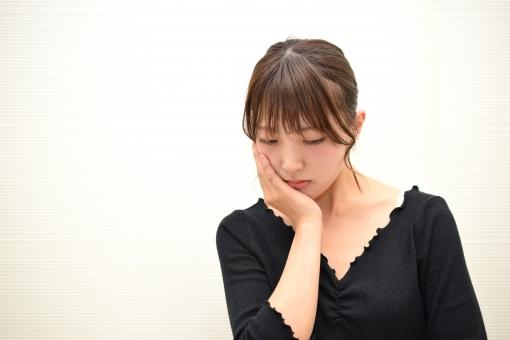 悩み事を抱える女性の写真