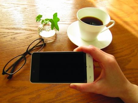 スマホ スマートフォン スマートホン 休憩 珈琲 ティータイム 手 ナチュラル 携帯 めがね 眼鏡 携帯電話 ケータイ メガネ 通信 カフェ 茶色 指 木目 横 コーヒーカップ スマフォ モバイル 横持ち