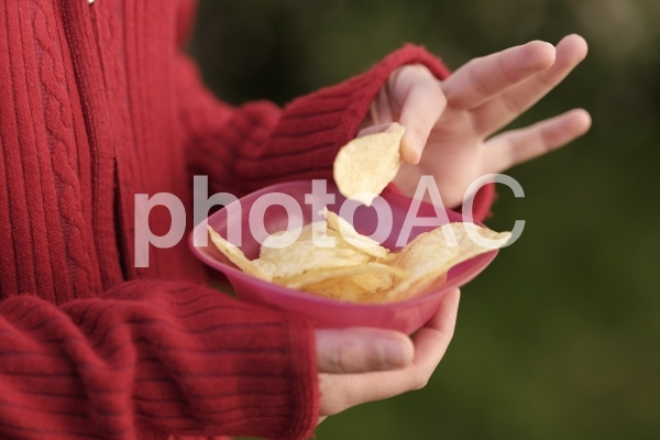 ポテトチップスを食べる女性の手元3の写真
