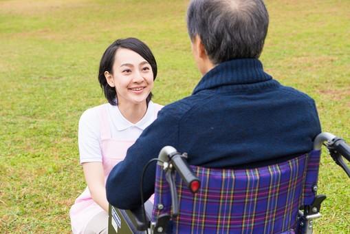 老人 高齢者 お年寄り シニア 男性 男 おとこ  2人 二人  介護士 看護師 エプロン  介護 不自由 椅子 ヘルパー 屋外 緑 木々 木 ジャケット ズボン 青  車いす 車椅子  女性 女 おんな 座る  握る 手 両手 散歩 外出 mdjf017 mdjms004