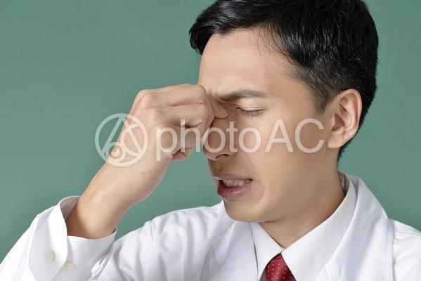 目が痛い白衣を着た男性1の写真