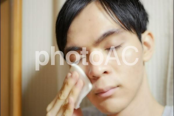 コットンで顔を拭く男性の写真