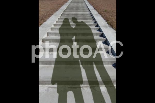 階段に伸びる男女の影の写真