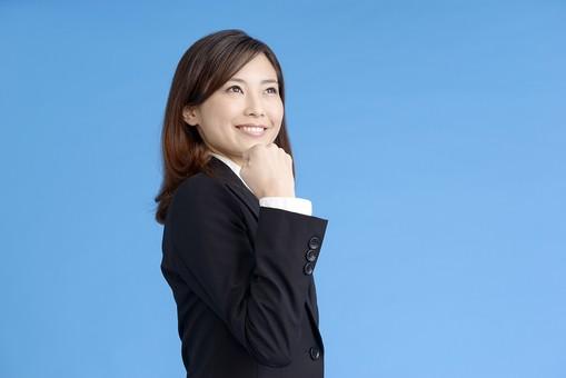 人物 女性 日本人 20代 若者  ビジネス スーツ 黒 紺色 セミロング  OL 社会人 会社員 ビジネスマン 就活  就職活動 真面目 ポーズ 屋内 スタジオ撮影  ブルーバック 上半身 ガッツポーズ 張り切る 頑張る やる気 力こぶ おまかせ 任せて 拳 こぶし 見上げる 笑顔 横向き mdjf013