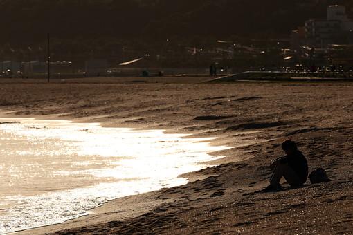 自然 海 水 海水 砂浜 砂 土 地面 打ち寄せる 波 水面 輝く 反射 綺麗 眩しい 人物 一人 座る 体育座り 孤独 寂しい 眺める 街並み 建物 建築 建築物 室外 屋外 風景 景色 景観 アート 芸術