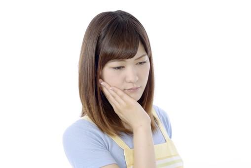 人物 屋内 白バック 白背景 日本人 1人 女性 20代 30代 エプロン  奥さん 奥様 婦人 家庭人 夫人 主婦 若い ポーズ 顔 表情 手 頬 顎 あご 当てる 手を顎に当てる 手を頬に当てる 歯痛 痛み 痛む 歯 不調  辛い mdjf018