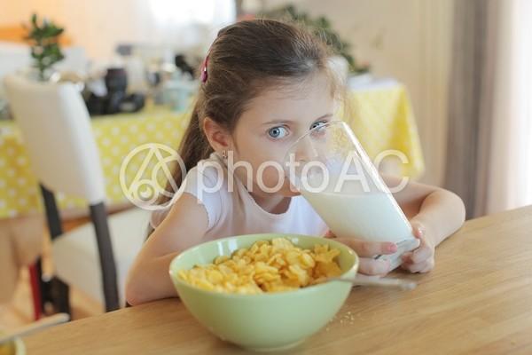 大きなグラスで牛乳を飲む女の子3の写真
