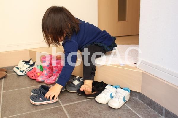 玄関で自分の靴を並べる子供2の写真