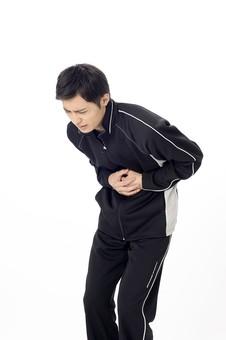 人物 人 男性 男 大人 日本人 20代 スタジオ撮影 白背景 白バック スポーツウェア ジャンバー ウィンドブレーカー  手 両手 腹 胃 腹部 押さえる 腹痛 胃痛 痛み 痛い さしこみ 吐き気 心配事 不調 くの字 苦痛 スポーツ 運動 mdjm025