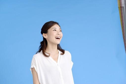 女性 ポーズ 人物 30代 日本人 黒髪 爽やか カジュアル 屋内 正面 ブルーバック 青背景 半そで 白  ほっとする 笑顔 微笑み 天を仰ぐ 歌う 上部目線 上機嫌 嬉しい 喜び 心地よい 快い mdjf013