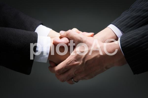 両手で握手するビジネスマンの写真