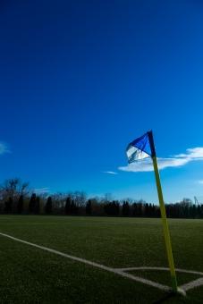 サッカー フットボール コーナーフラッグ コーナー コーナーキック フラッグ コーナーポスト 蹴球 ピッチ 芝 グラス 青空 スカイ 快晴 晴れ 太陽 はためき グラウンド グランド サッカー場 スポーツ 屋外 競技場