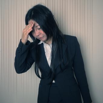 頭を抱えるスーツの女性の写真
