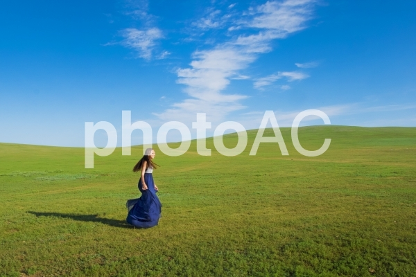 モンゴルの大地を駆ける青いドレスの女性の写真